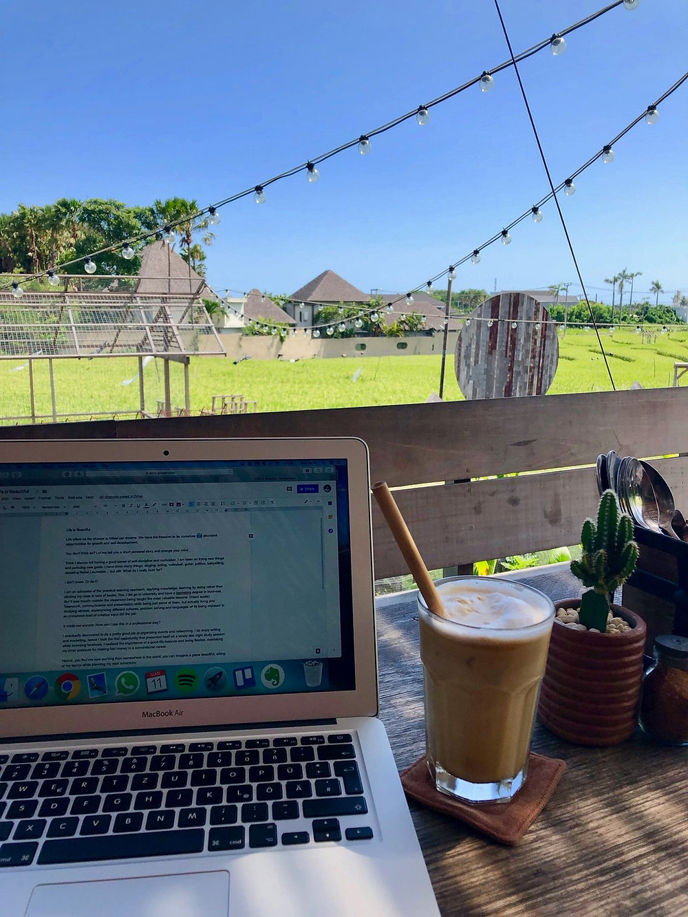 Laptop and vegan iced coffee with view of a rice field