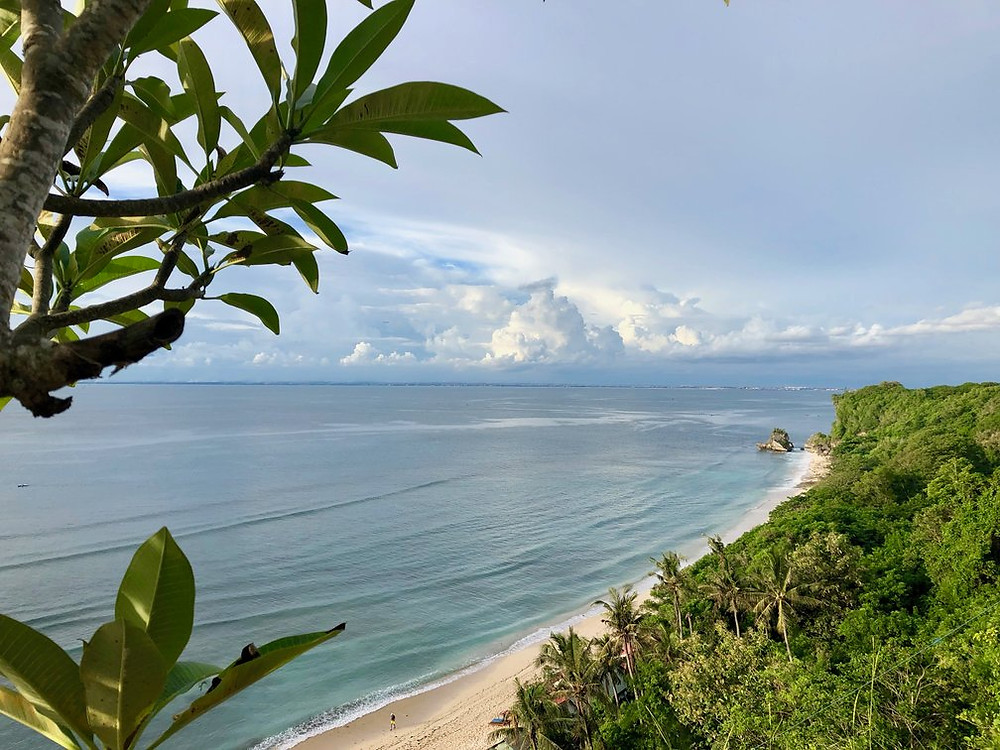 Long stretch of white beach and blue ocean