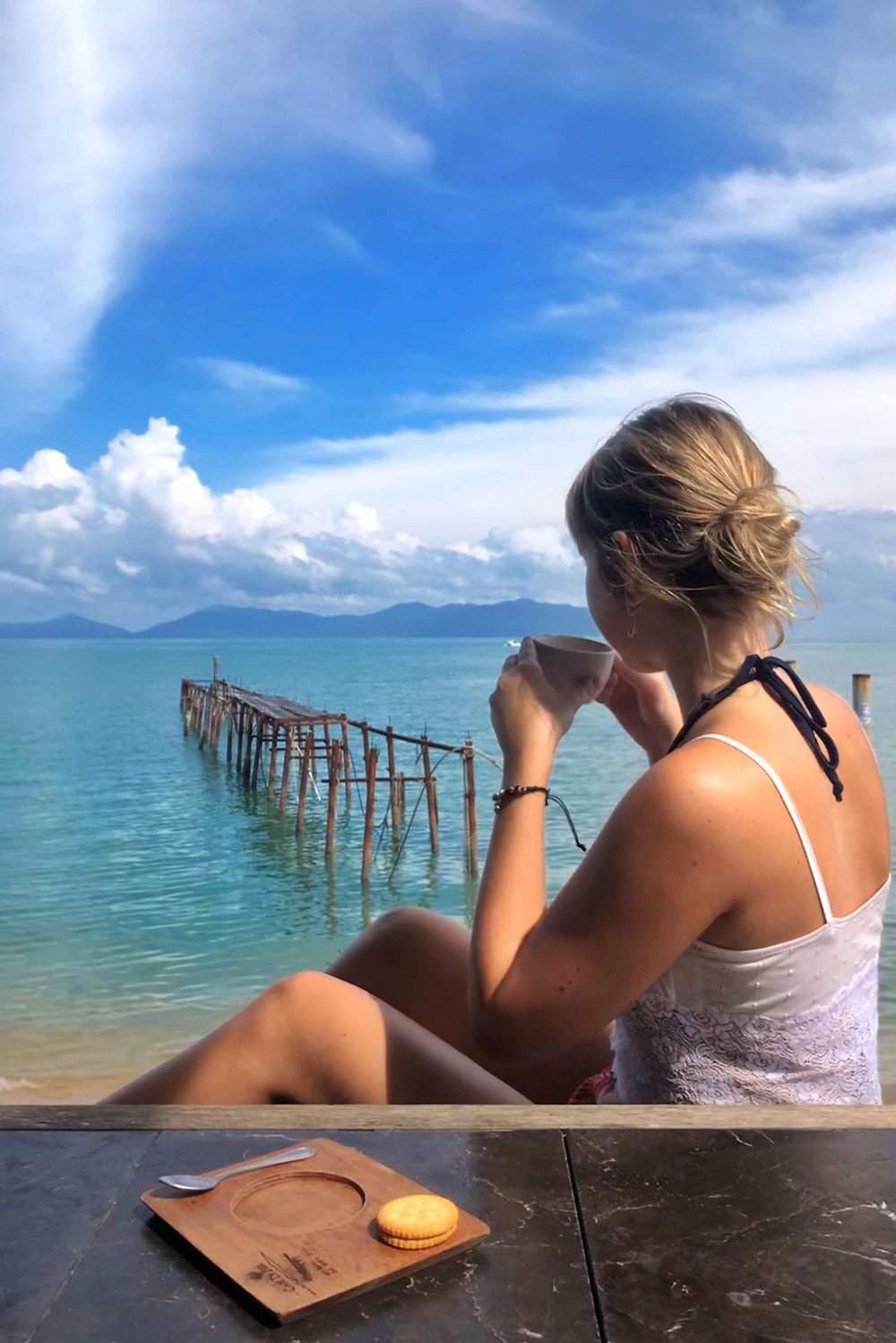 Girl drinking coffee by the ocean