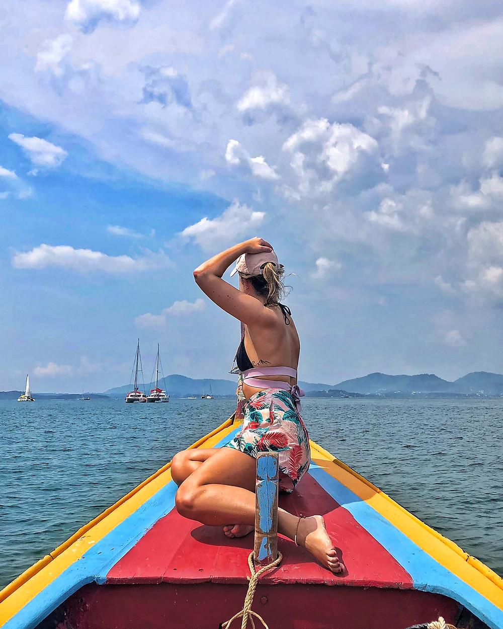 Girl on a colourful boat holding her hat with one arm