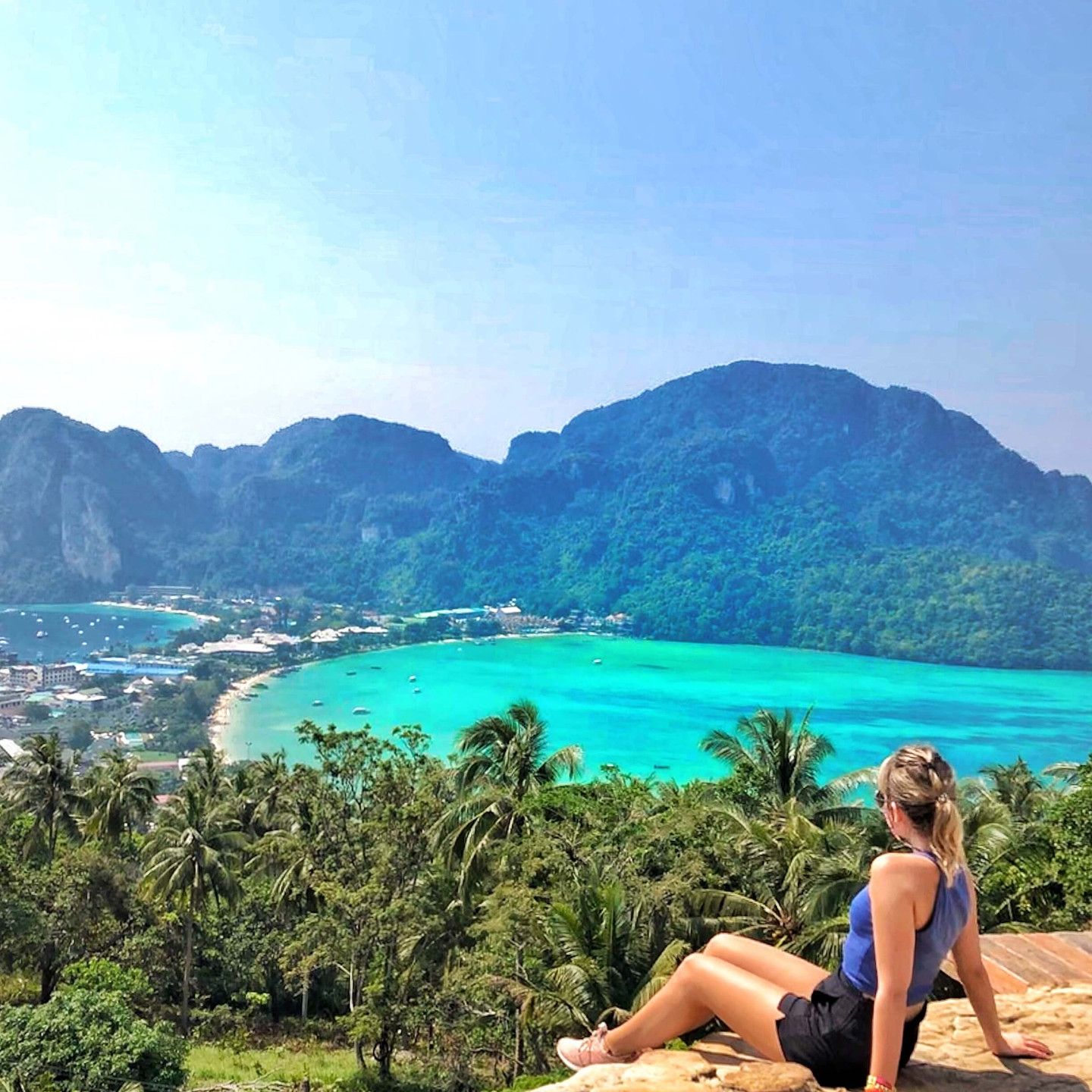 Girl sitting on a rock with view of tropical island