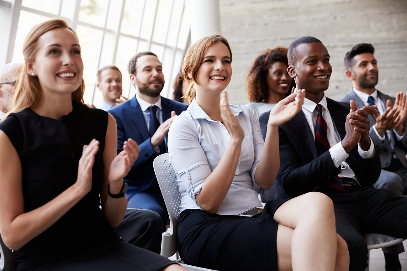 Diverse audience clapping at a business presentation