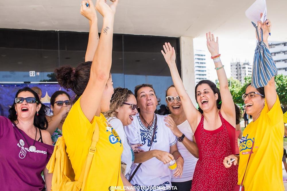 8 mulheres riem e levantam os braços. Algumas vestem a camiseta amarela do clube do riso de Recife