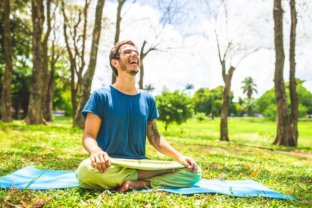 Sandro está sentado em posição de meditação sobre um tapete de Yoga azul na grama de um amplo jardim.