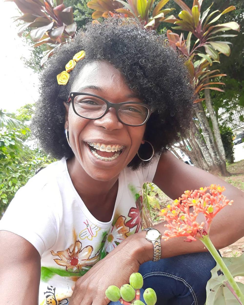 Mulher negra rindo uma risada com aparelho, relógio de pulso e Yoga do Riso entre as flores