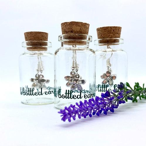 Silver daisys on sterling silver hooks in a glass bottle