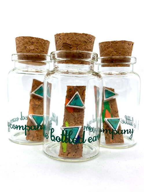 silver and turquoise triangle stud earrings in a glass bottle