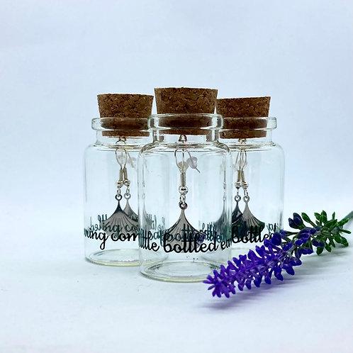Silver deco style earrings in a glass bottle