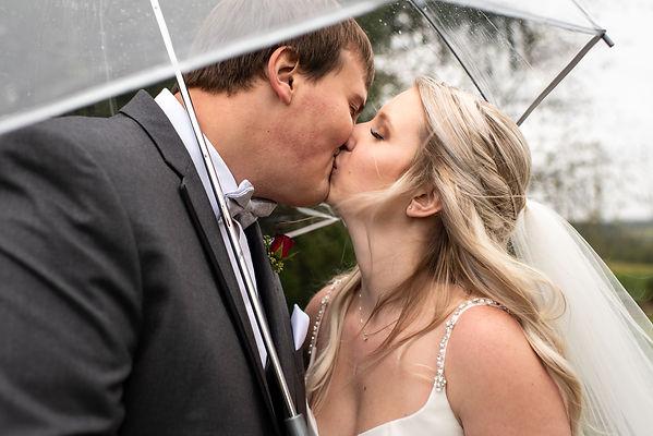 Moody rainy wedding with umbrella and kisses in Everett, PA