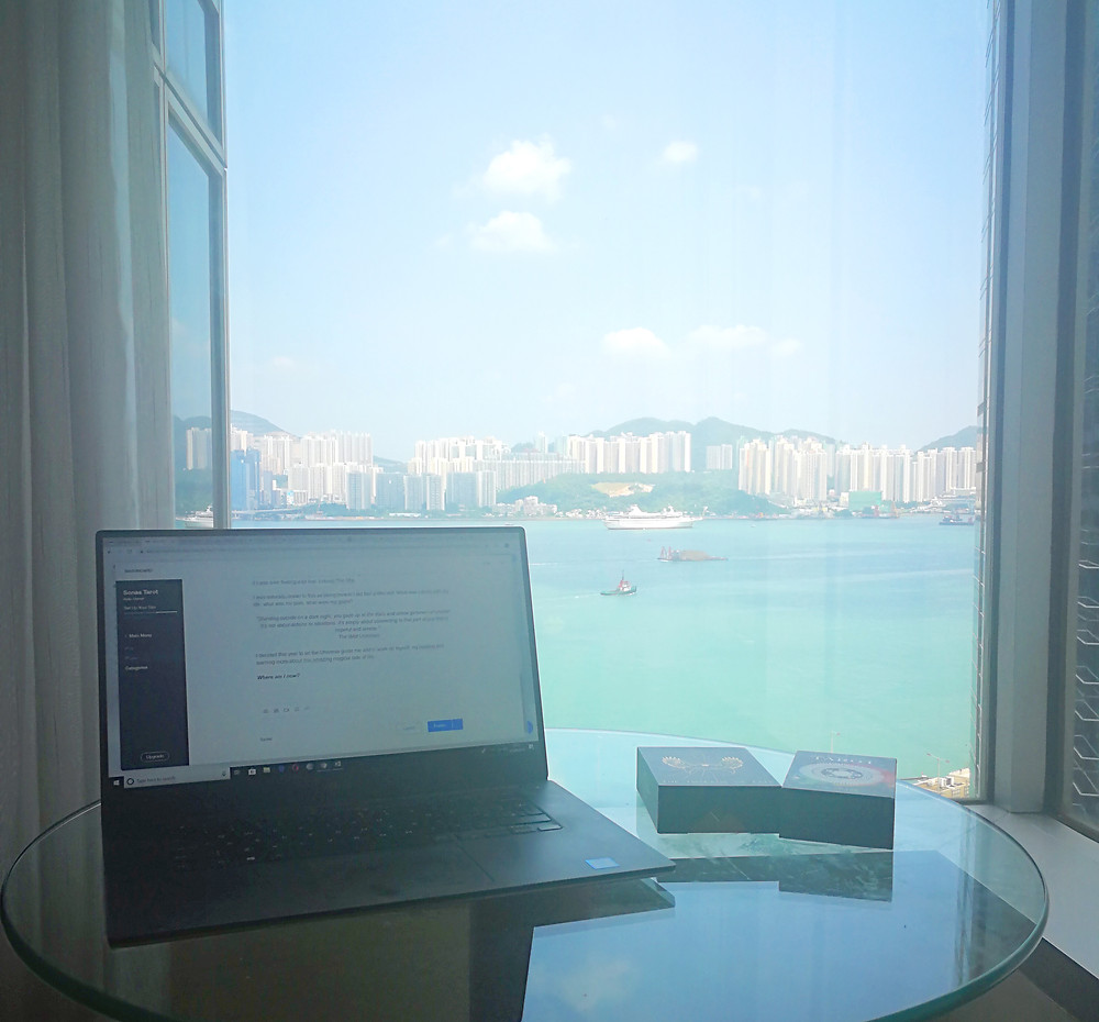 A view of the Harbour in Hong Kong. A laptop and two decks of Tarot card sit on a glass table.