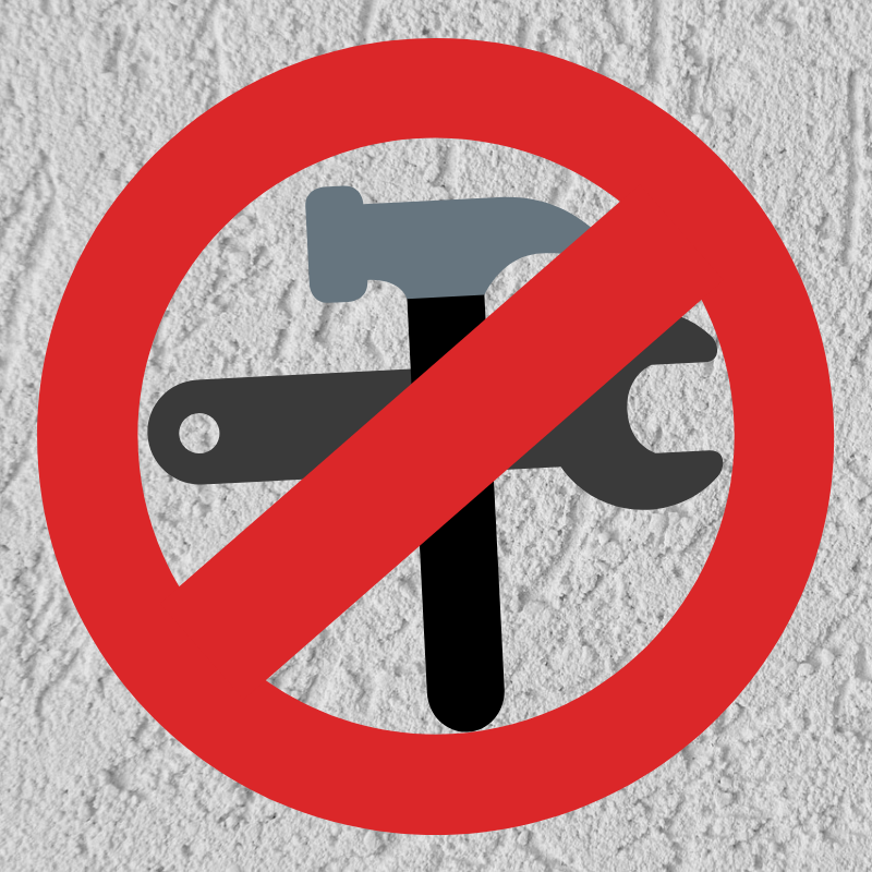 Red Circle with Line through it at an angle, over a wrench and hammer with a stucco background