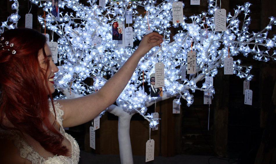 The bride hanging her wishing tag on our 8ft illuminated wishing tree