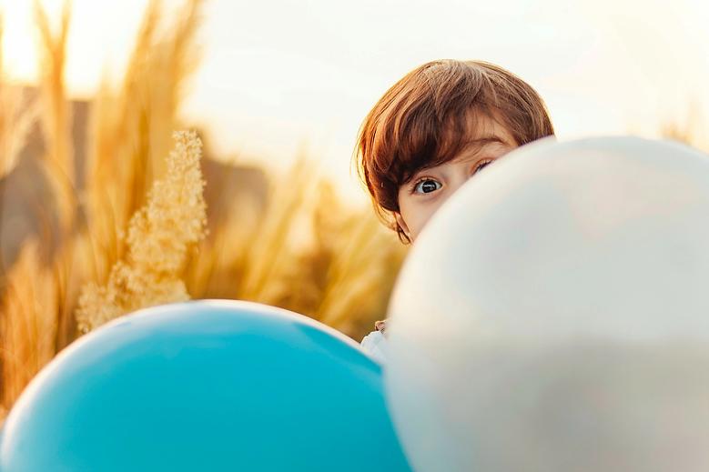child peeking out behind balloons.webp