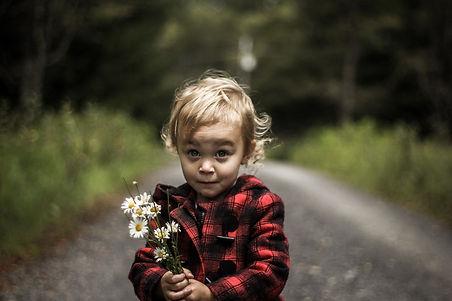 un enfant avec un bouquet de fleurs