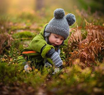 petit garçon joue dans l'herbe en automne