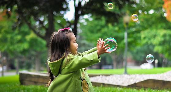 petite fille qui joue avec des bulles de savon dehors