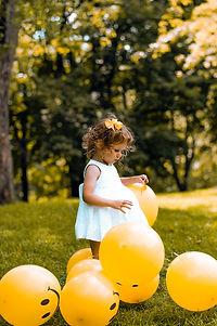 petite fille joue avec des ballons jaunes
