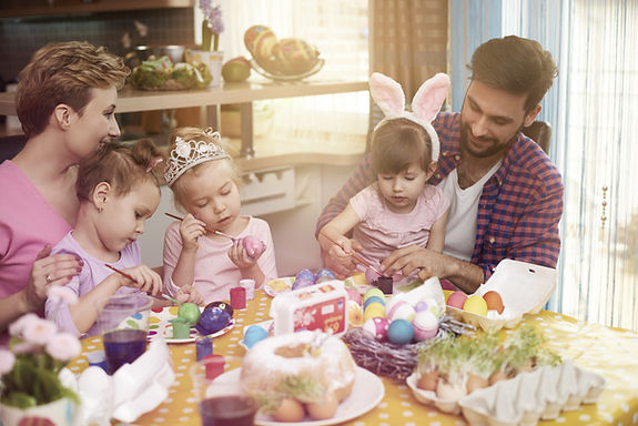 A family sitting around a table painting easter eggs.