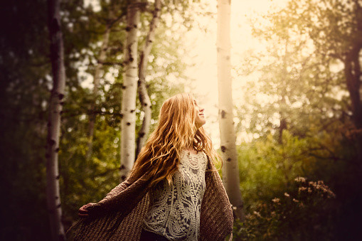 Girl taking in nature in the forest for relaxation, health and wellbeing