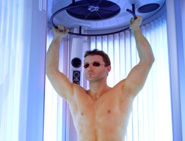 Man in a stand-up tanning booth at World Gym in Palm Springs