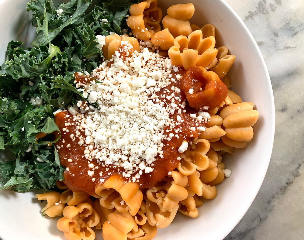 Pumpkin Pasta Sauce in a bowl with kale on a marble background