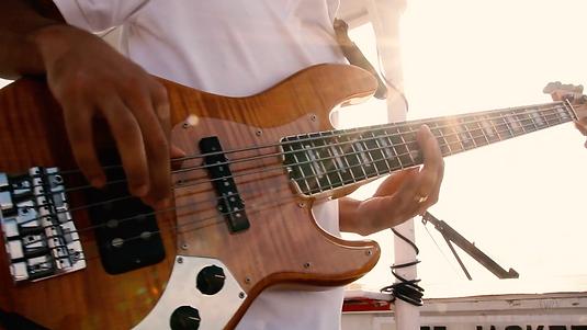 Close up on hands playing bass. Sun rays  shinning through.