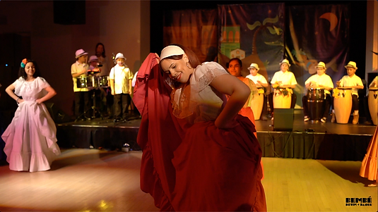 Woman dancing in foreground holding her skirt up. Kids playing drums  and dancing in the background