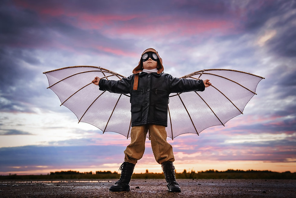 Boy with wings at sunset imagines himsel