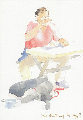Man drinking at an outdoor table with dog laying at feet
