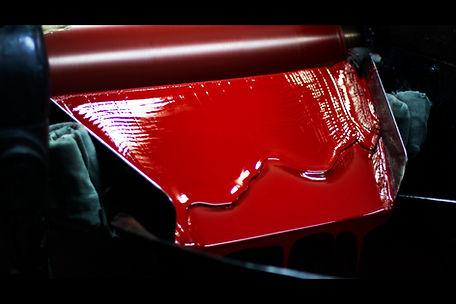 Molino tricilíndrico en el cual se observa abundante tinta roja deslizándose hacia abajo.