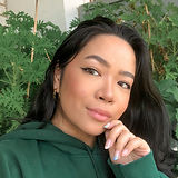 Image Description: woman modelling gold hoop earrings from Mejuri. She stands in front of green plants, wearing a green hoodie.