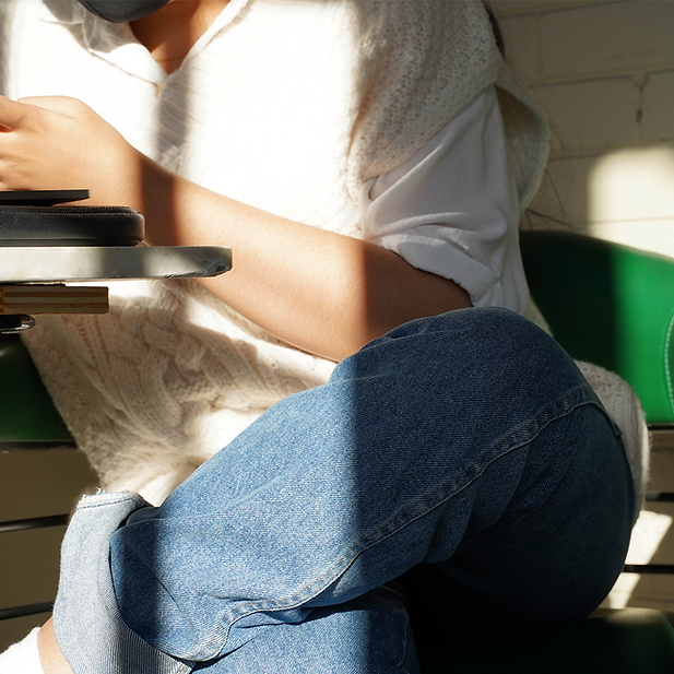 Alt Text: Jillian Maniquis sitting down while on laptop, wearing a white t-shirt and blue jeans.