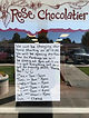 New business hours are posted on the door at Rose Chocolatier.