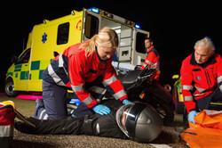 Paramedical team assisting injured man motorbike driver at night.jpg