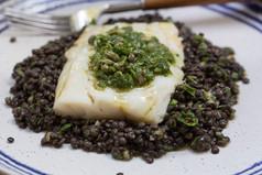 Pan-seared seasonal fish with black lentils and salsa verde