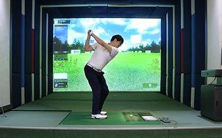 A  man enjoying screen golf with 7-iron