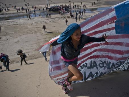 Emigrantes intentan cruzar muro con Estados Unidos y reciben gas lacrimógeno