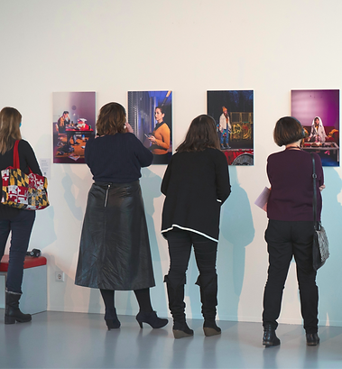 Four women in back view at a photo exposition all wearing headphones are looking at OmniStill images