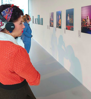 Two women at a photo exposition wearing headphones and looking at OmniStill images
