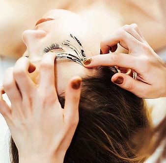 Kinesiotape wird angebracht auf Gesicht einer jungen Frau