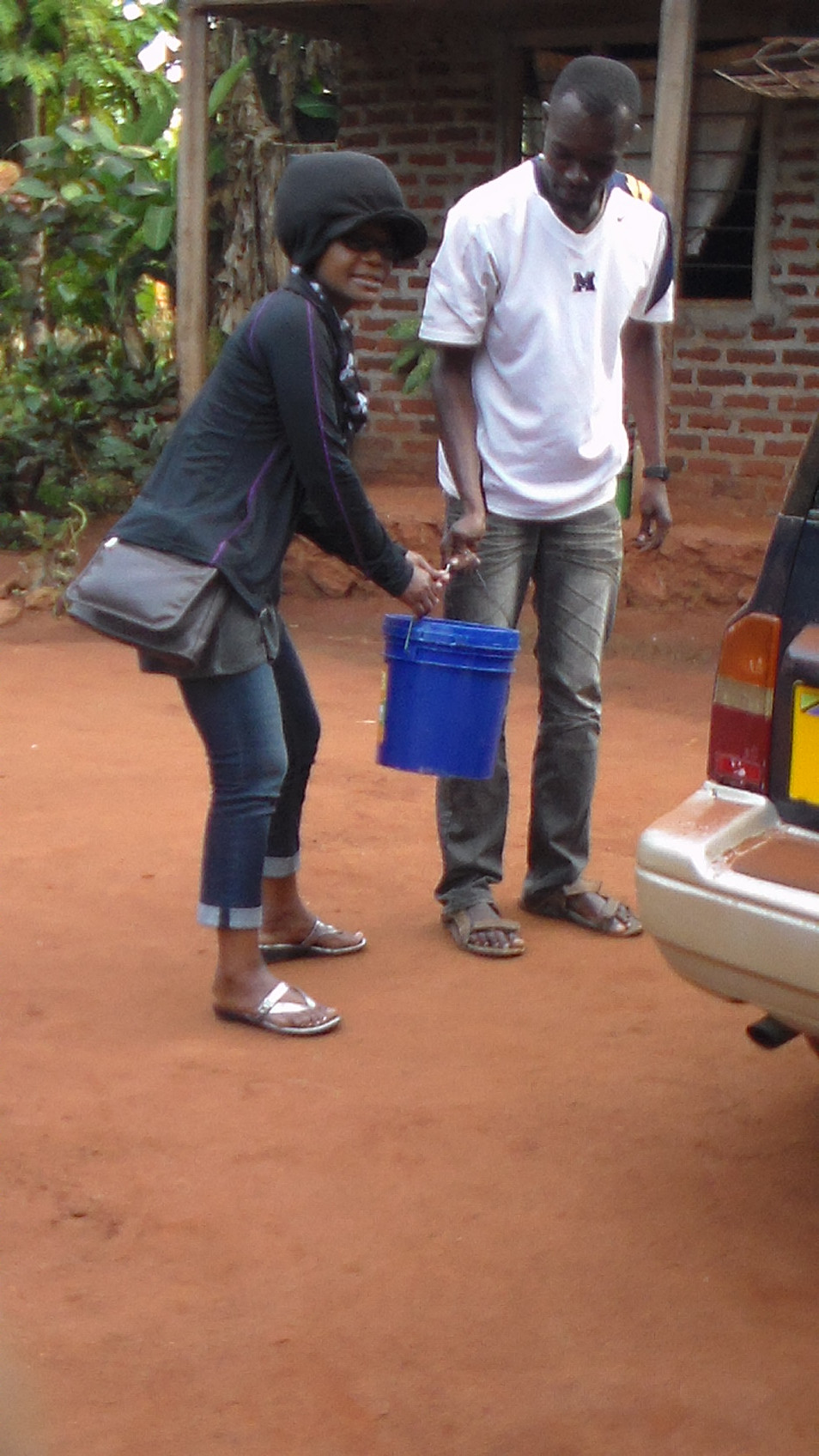 Étu helping to deliver water to the village