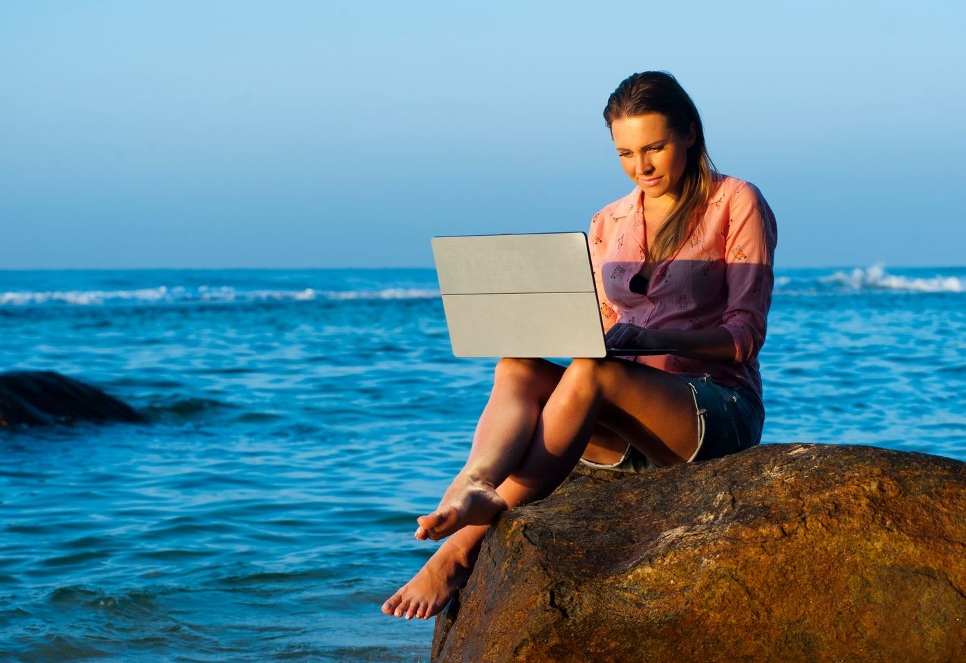 Work from beach - lady with laptop sitti