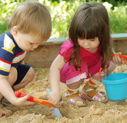 Boy and girl in sand pit