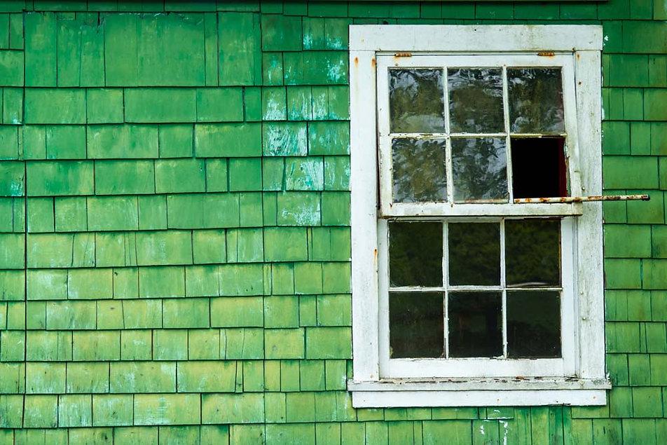 Rustic green shack and broken window in Bamfield Vancouver Island
