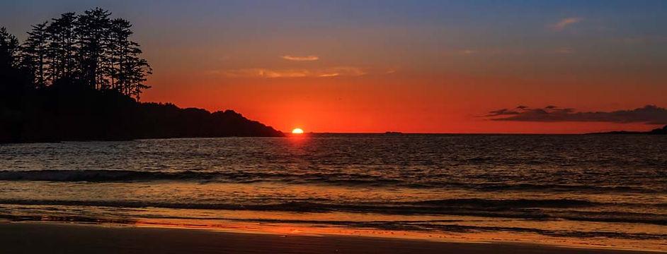 Red Sun falls into ocean at Chesterman Beach in Tofino, BC