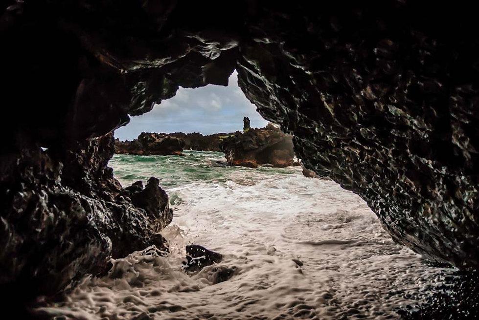 Turbulant sea rushes into sea cave, Maui, HI