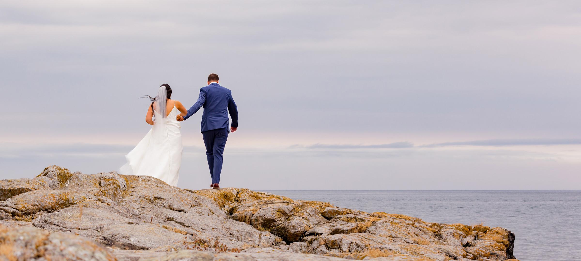 Bride & groom walk towards water