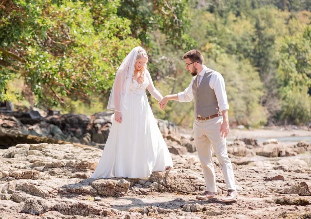 Groom helps Bride on rocks