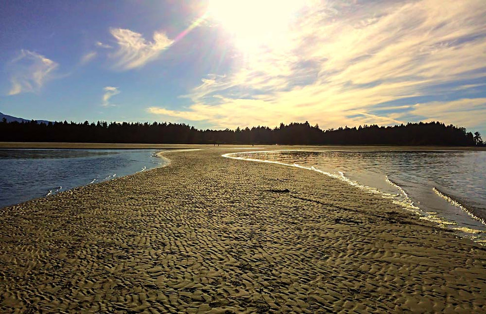 Sandbar path divdes the ocean leading to the sunset at Rathetrevor Beach near Nanaimo BC