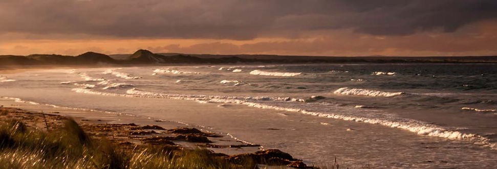 Orange sunset over misty waves in Northern Scotland